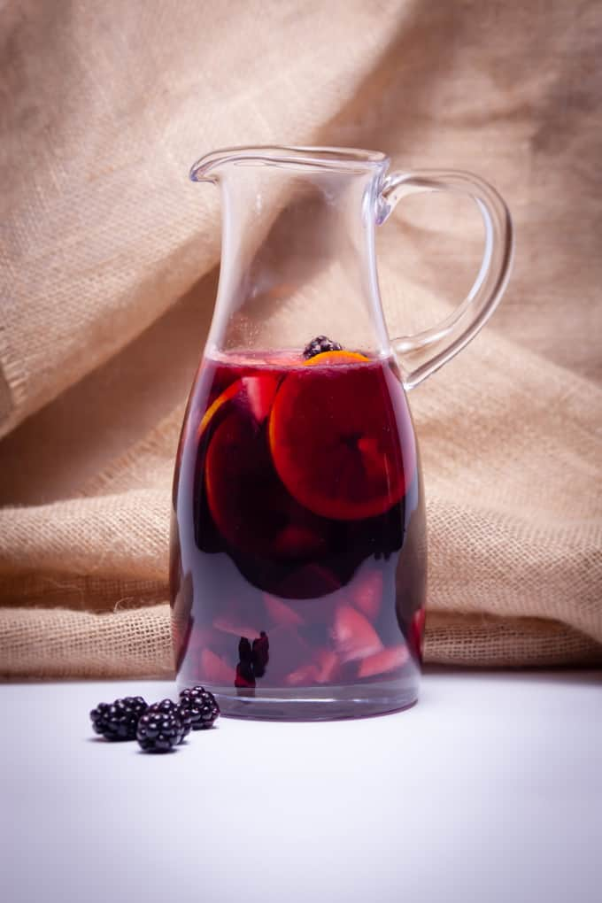 Red wine sangria in a pitcher with blackberries and burlap background