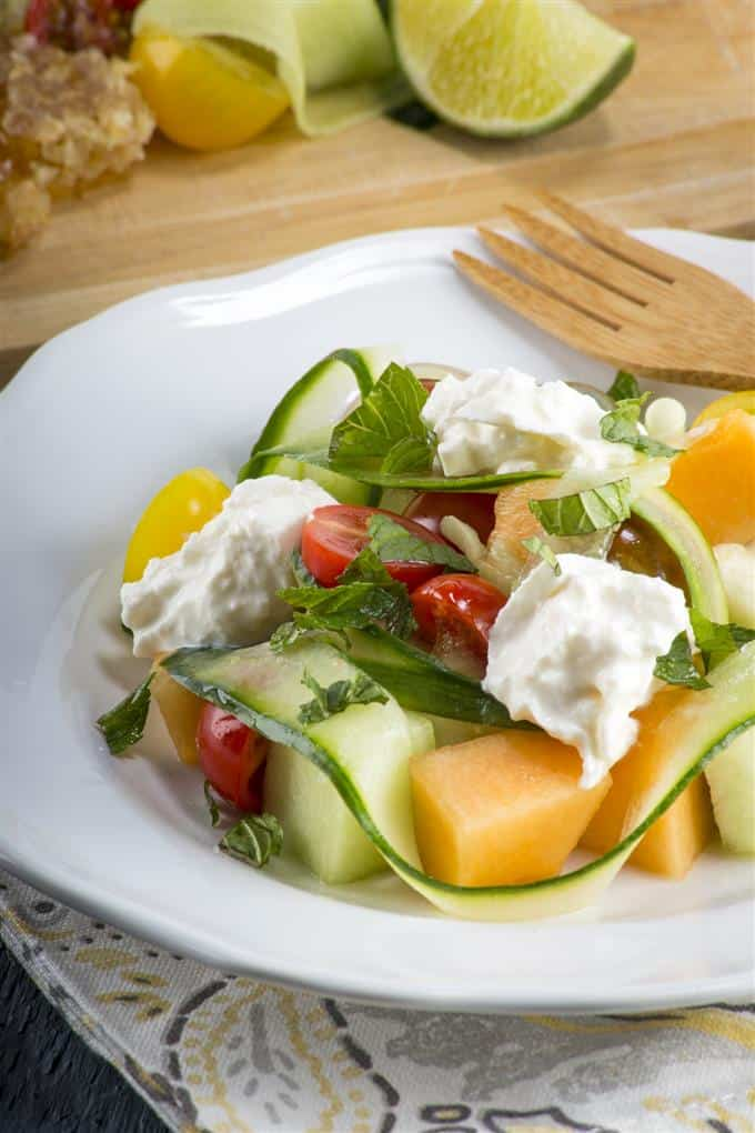 Colorful heirloom tomatoes, melon, and burrata combine for an elegant but easy summer salad