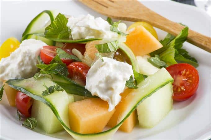 Colorful salad with heirloom tomatoes, melon, cucumber and creamy burrata cheese