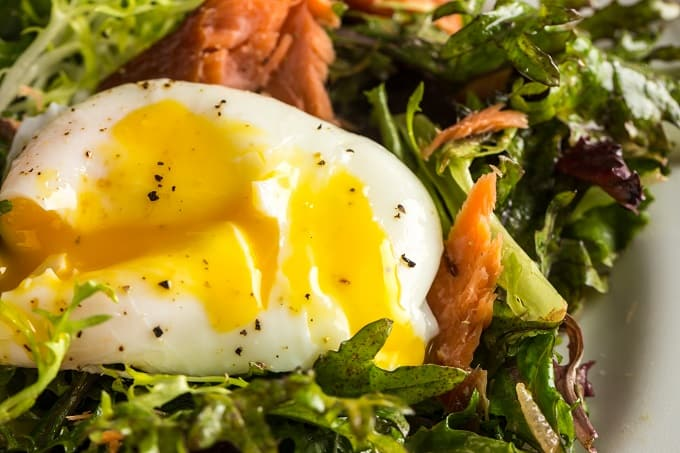 Perfectly poached egg on this salmon Lyonnaise salad